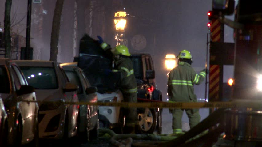 MONTREAL, QC - 1/2014 - 4K 60fps - Firemen covering car with tarp. Two fire-fighters cover a vehicle to protect it while fighting a fire with trucks and ladder and smoke in the background.