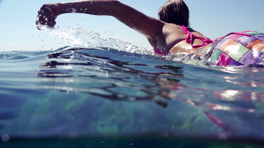 SLOW MOTION: Female surfer paddling out