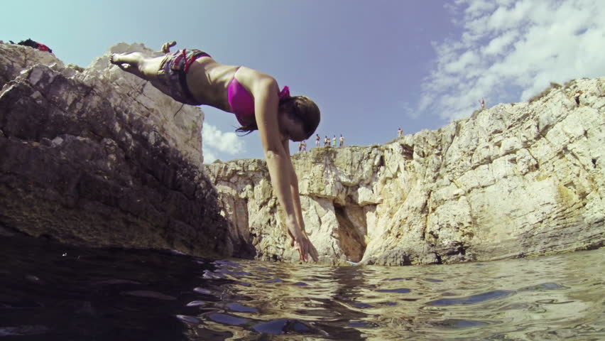 SLOW MOTION: Young woman jumping into the ocean