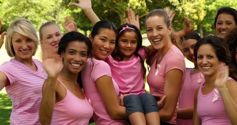Happy women in pink for breast cancer awareness in the park waving at camera on a sunny day