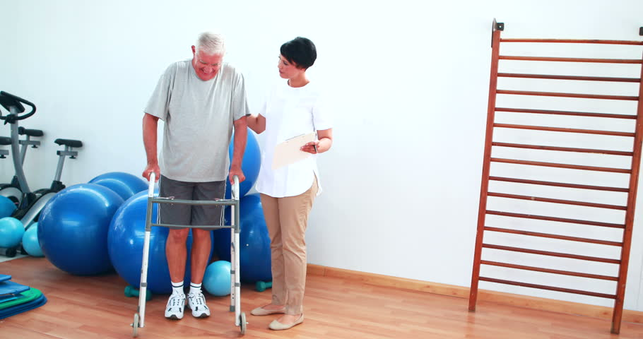 Smiling physiotherapist helping patient walk with walking frame at the rehabilitation center