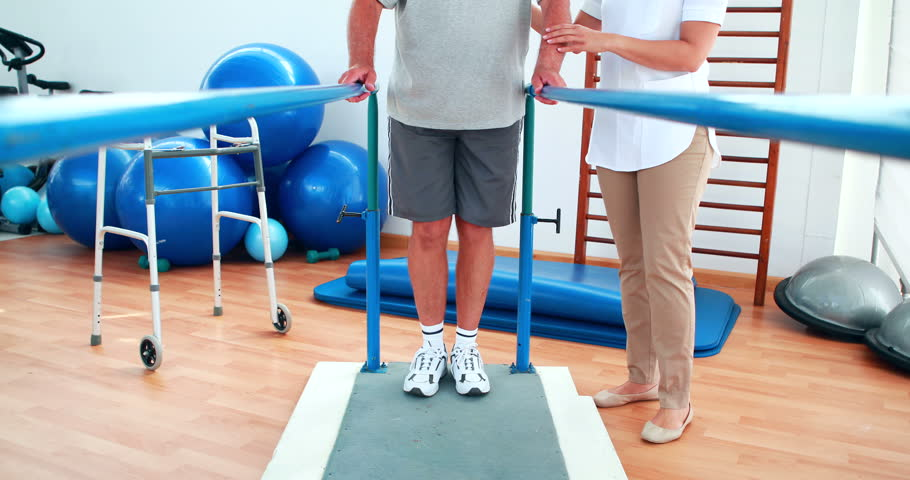 Physiotherapist helping patient walk with parallel bars at the rehabilitation center