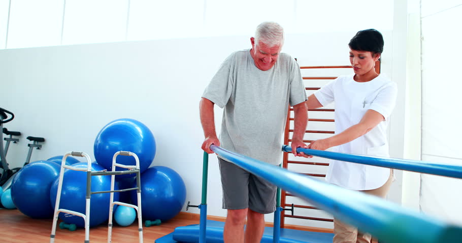 Smiling physiotherapist helping patient walk with parallel bars at the rehabilitation center