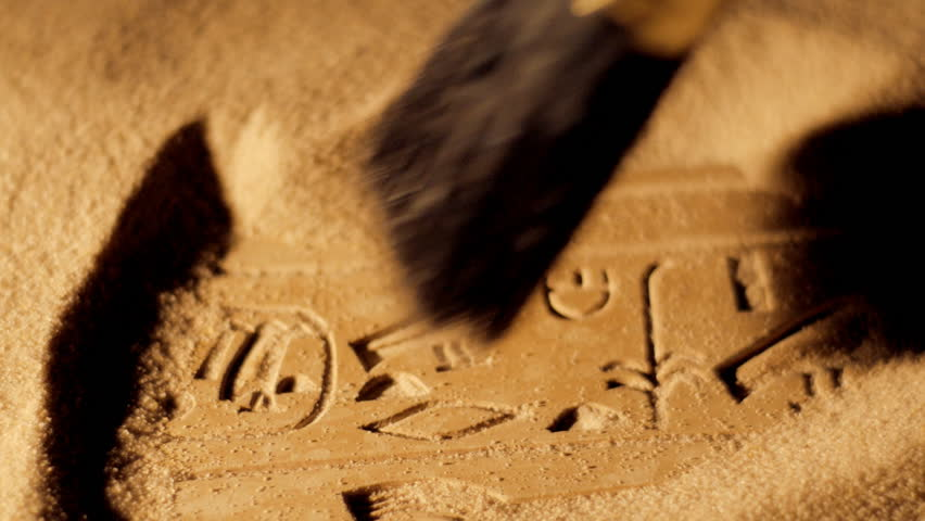 Tracking shot of archaeologist brushing sand from ancient Egyptian hieroglyphics Royalty-Free Stock Footage #5666105