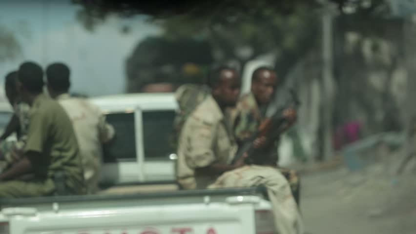 Mogadishu, Somalia, Circa 2013: A Toyota pickup full of armed Somali soldiers pass a transporter truck on the streets of Mogadishu, Somalia, Circa 2013.