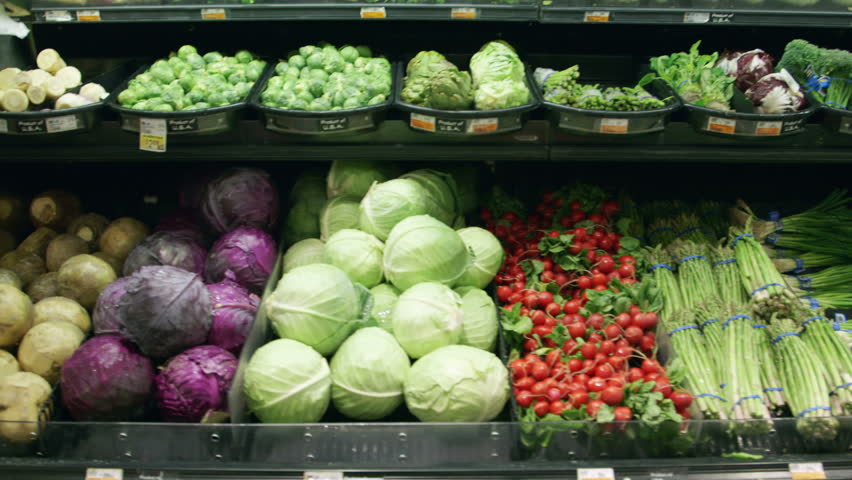 Medium shot moving past fresh vegetables in a supermarket grocery. Includes cabbage, celery, broccoli, lettuce, carrots, corn, onion, etc. Wide shot and close-up of same set-up are in my portfolio.