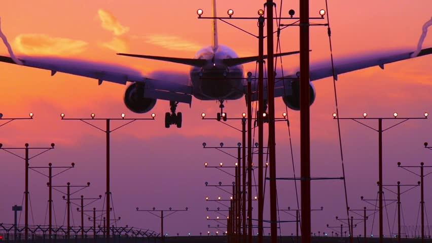 Airplane jet plane landing in airport at beautiful sunset, producing wake vortex turbulence. Slow motion. | Shutterstock HD Video #5697263