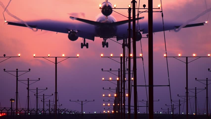 Airplane jet plane landing in airport at sunset. Slow motion.