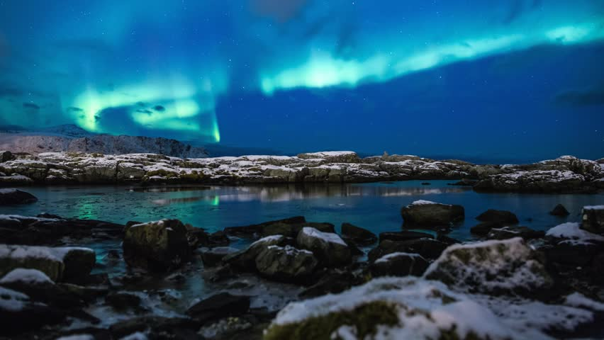 Northern lights above rock pools on the coast or Norway