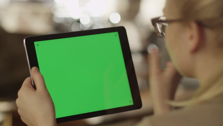 Girl Using Tablet PC with Green Screen. Shot on RED Digital Cinema Camera in 4K (ultra-high definition (UHD)), so you can easily crop, rotate and zoom. Easy for tracking and keying. ProRes HQ codec.  | Shutterstock HD Video #5793359