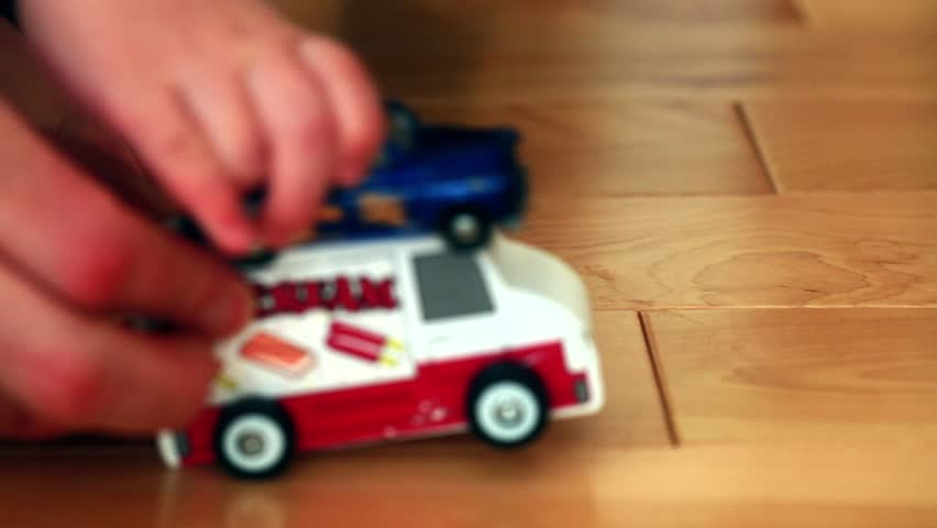 A father playing toy cars with his toddler close up shot