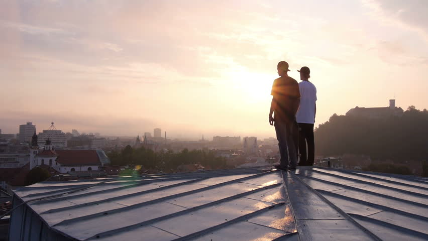 AERIAL: Two young skateboarders standing on rooftop Royalty-Free Stock Footage #5807138