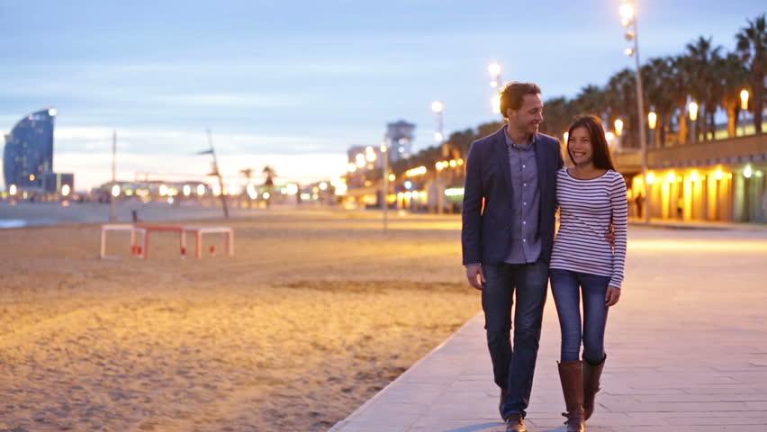 Couple walking at Barcelona Beach, Barceloneta at night enjoying romantic evening holding hands in love. City lifestyle multiracial couple, Asian woman, Caucasian man. #5807564