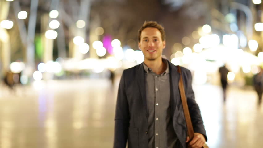 Business man giving thumbs up success hand sign. Happy smiling casual businessman walking into focus smiling happy and successful at night on La Rambla, Barcelona, Spain. Young casual professional man
