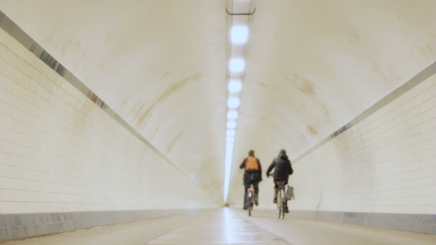 Static shallow depth of field low angle shot of anonymous cyclists cycling on their bicycles into a long circular round concrete pipe shaped tunnel illuminated by a line of ceiling lights.