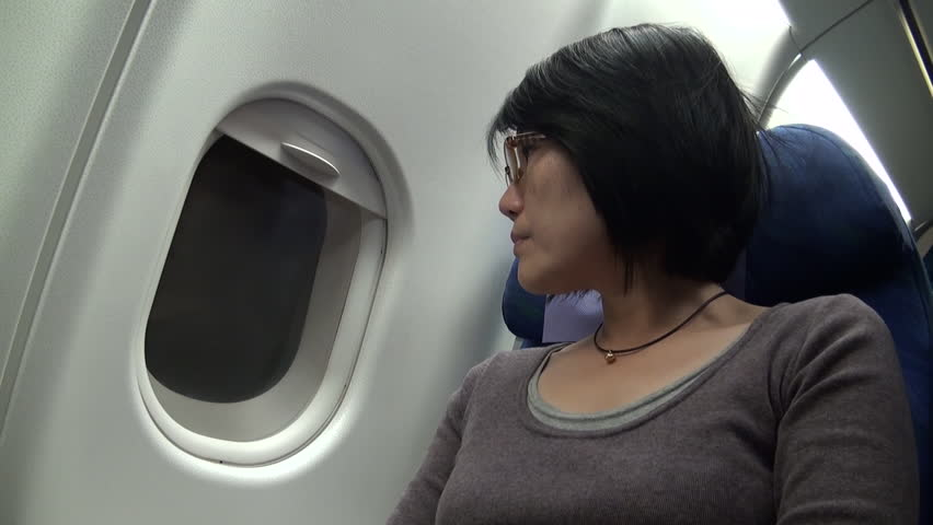Chinese woman open and shut the blind of a window plane