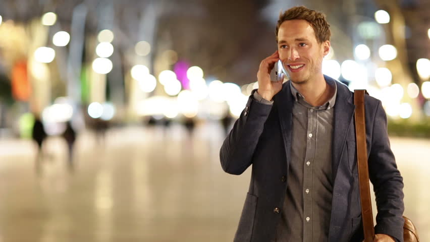 Smart phone man calling on mobile phone at night on La Rambla in Barcelona, Spain. Handsome young business man talking on smartphone and walking away smiling happy wearing suit jacket outdoors. | Shutterstock HD Video #5815799
