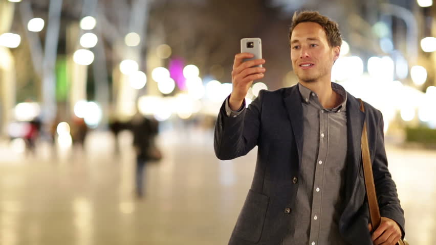 Man taking photo with camera phone at night on La Rambla, Barcelona, Spain. Young casual man taking picture with camera phone outside.
