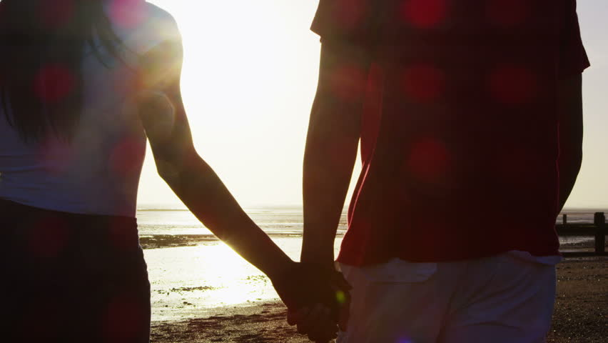 Romantic young couple holding hands and walking on the beach as the sun begins to set. In slow motion. | Shutterstock HD Video #5841446