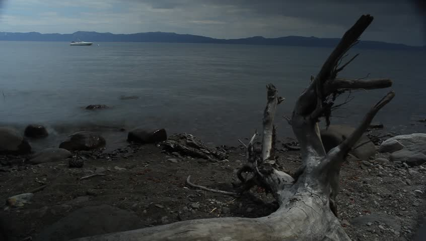 Lake Tahoe, California - August, 2012 - Time-lapse of water washing up on the beach with a fallen tree in the foreground by McKinney Bay Pier.