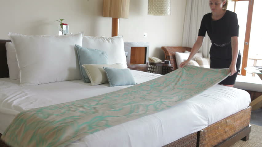 Chambermaid arranges cushions in hotel bedroom.Shot on Canon 5d Mk2 with a frame rate of 30fps