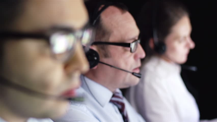 Three operator consulting clients online in call center