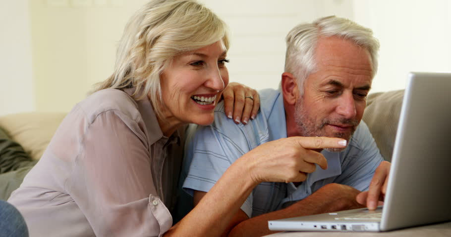 Cheerful couple using laptop together at home in the living room | Shutterstock HD Video #5936123