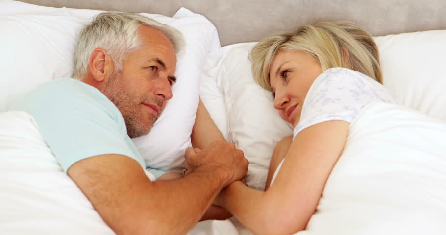 Happy couple chatting and holding hands in bed at home in bedroom | Shutterstock HD Video #5936498