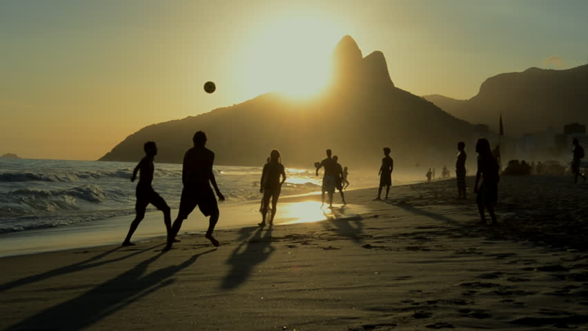 Silhouettes of Carioca Brazilians playing altinho keepy uppy beach football at sunset on Ipanema Beach Rio de Janeiro Brazil | Shutterstock Video #5974397