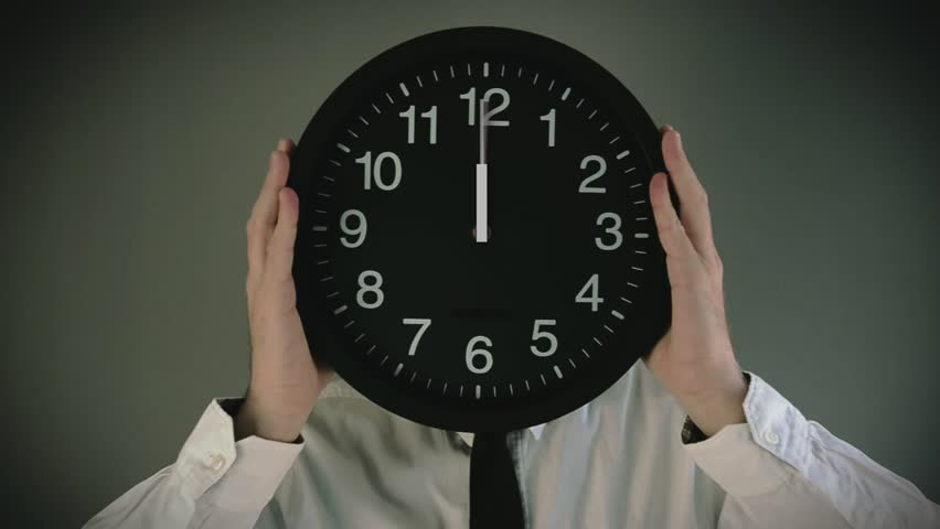 Time management. Businessman with clock in front of his head wand clock hands going round in full turn. Deadline concept of worker with not enough time to finish the job.