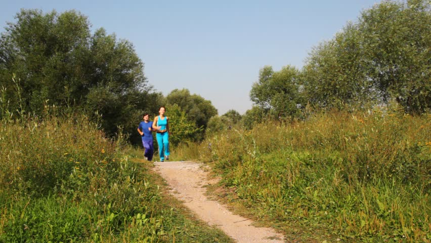 Man and woman run back on path in park  | Shutterstock HD Video #599233