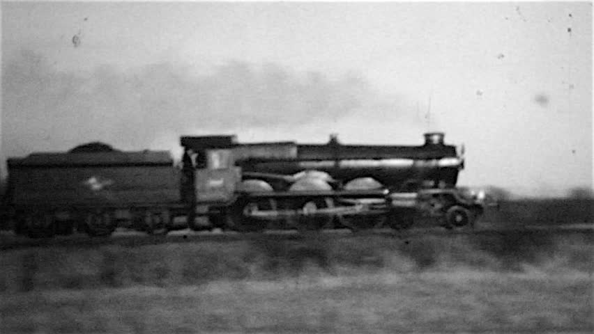 Old steam train. A Great Western Railway steam locomotive engine hauling an express passenger train through the countryside. A grainy old black and white film circa 1960 in Northamptonshire England UK