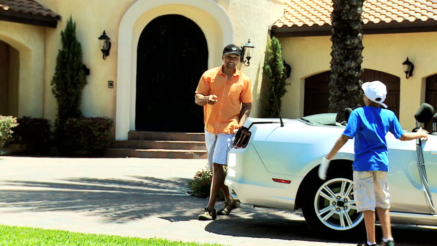 Happy African American father young son arriving home in luxury convertible car after day together with golf clubs - Ethnic Father Young Son Returning Golf Luxury Car