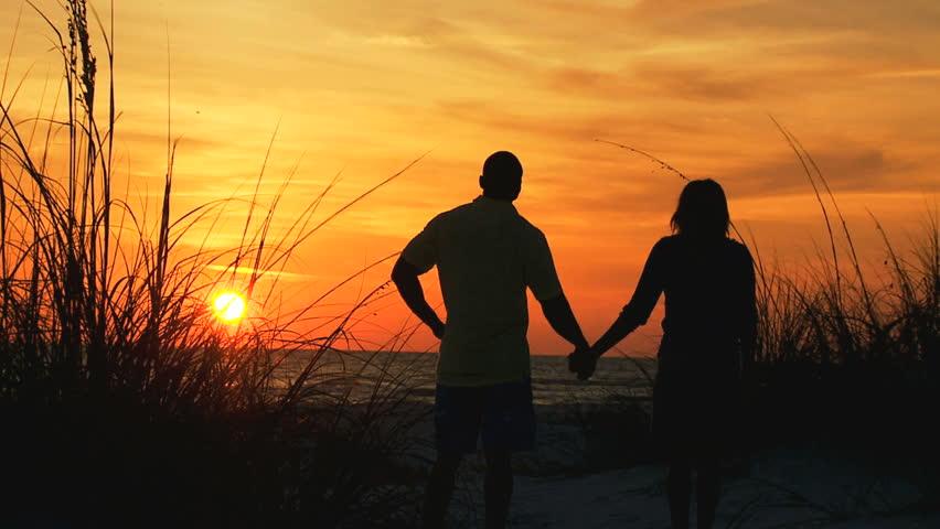 Silhouette of loving Latin American couple enjoying sunset