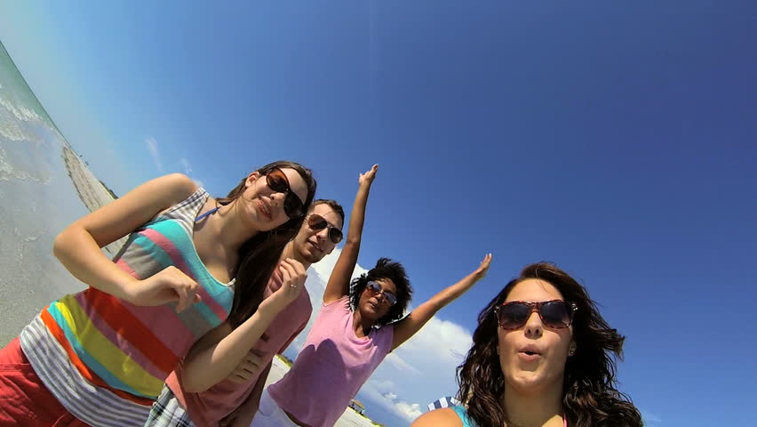 Happy young multi ethnic teens outdoors on vacation greeting friends using social media using wide angle camera shot on RED EPIC - Laughing Young Multi Ethnic Teenage Friend Filming Beach | Shutterstock HD Video #6003383
