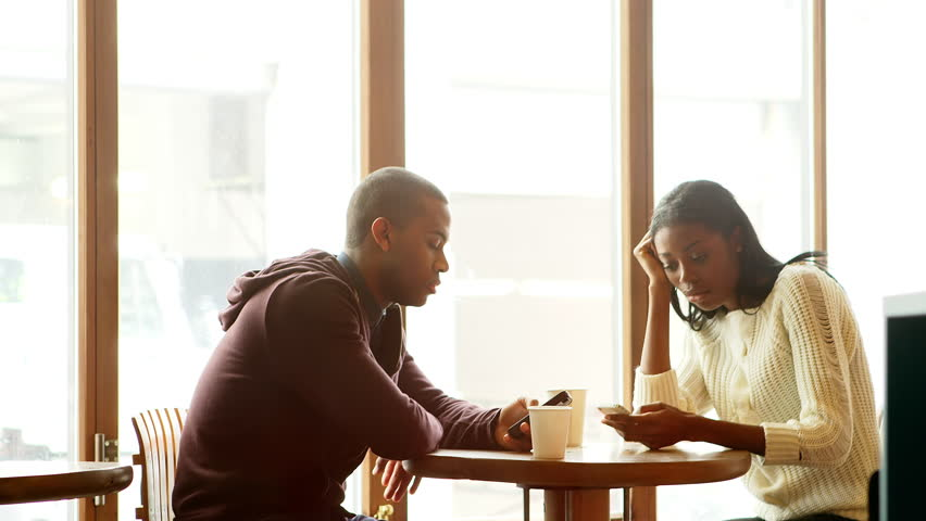 Wide shot of a woman looking at her date who is not paying attention to her while he is on his phone in a cafe   Shutterstock HD Video #6015944