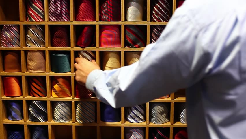Front shot of a tie collection and a man picking up a tie for his shirt/A darker one or...