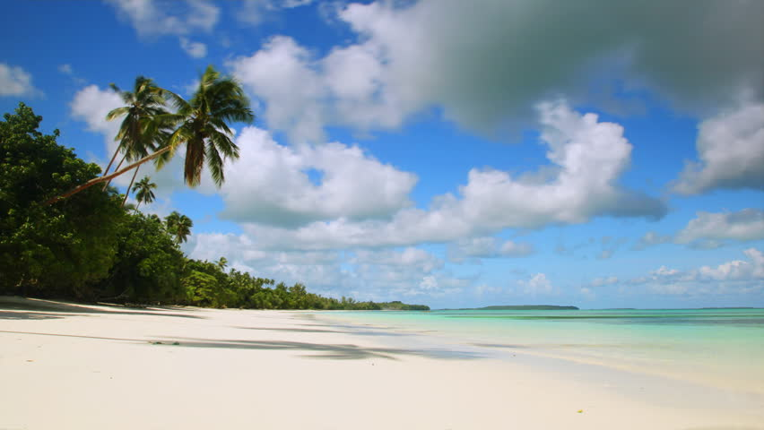 Time-lapse of white sand tropical beach with turquoise water, coconut trees swaying in the wind and clouds passing by.   Shutterstock HD Video #6039092