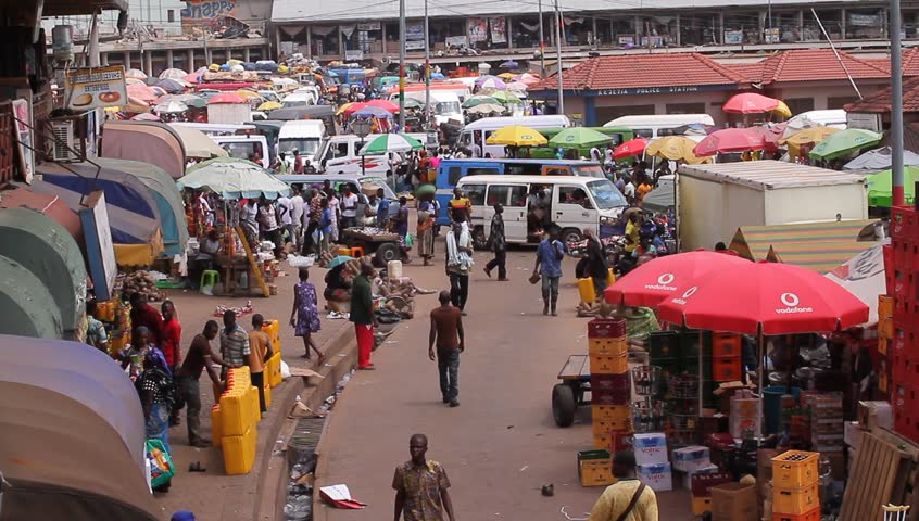 KUMASI, GHANA AFRICA  - MAY 2013, wide shot of a lorry park, market people walking