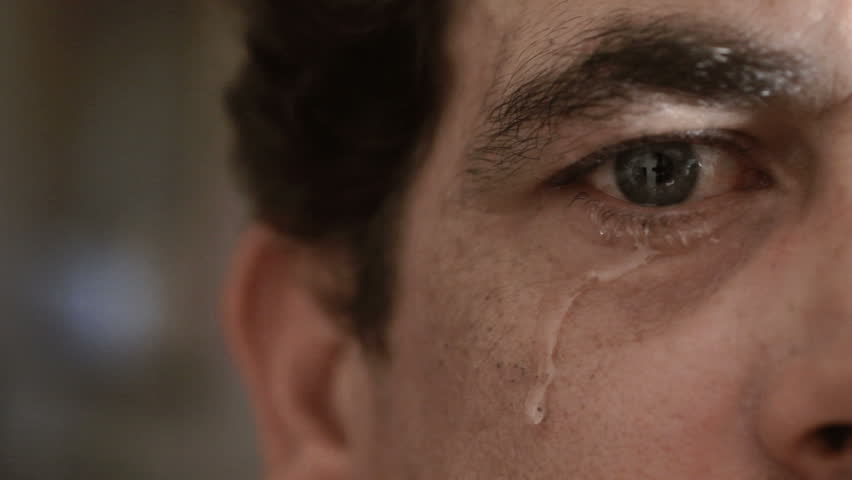 Crying man with tears in eye closeup