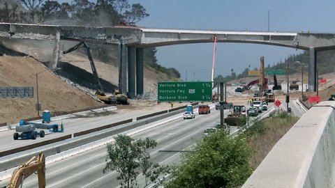 LOS ANGELES, CALIFORNIA, CIRCA 2013 - Zoom out and pan right to left over an empty stretch of the 405 freeway in Los Angles as crews tear down part of a bridge.