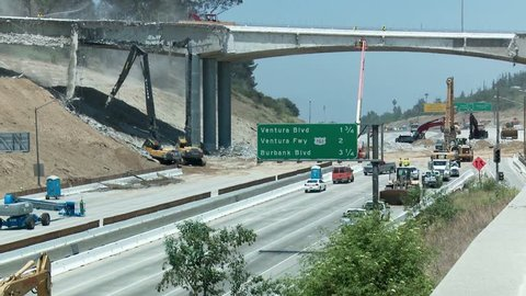 LOS ANGELES, CALIFORNIA, CIRCA 2013 - View of heavy equipment tearing down part of a bridge over the 405 freeway in Los Angles.