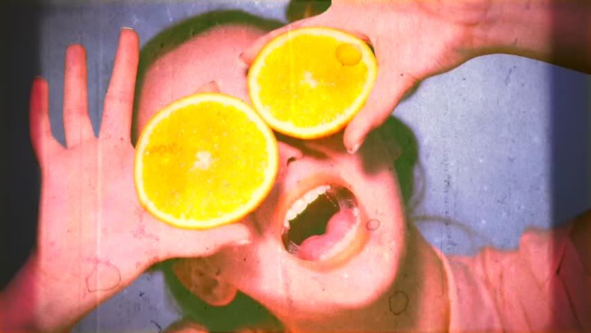 Beauty Model Girl takes Juicy Oranges. Beautiful Joyful teen girl with freckles, funny red hairstyle and yellow makeup. Professional make up. Orange Slices. Old Styled Film in fast motion. Silly Vintage Beauty Theme.