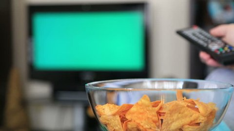 Woman Watching Chromakey TV And Eating Potato Chip