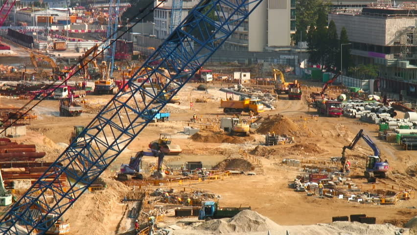 Heavy equipment and workers roam a construction site (timelapse)