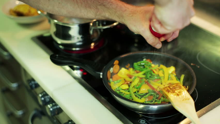 man's hands seasoning vegetables in a frying pan