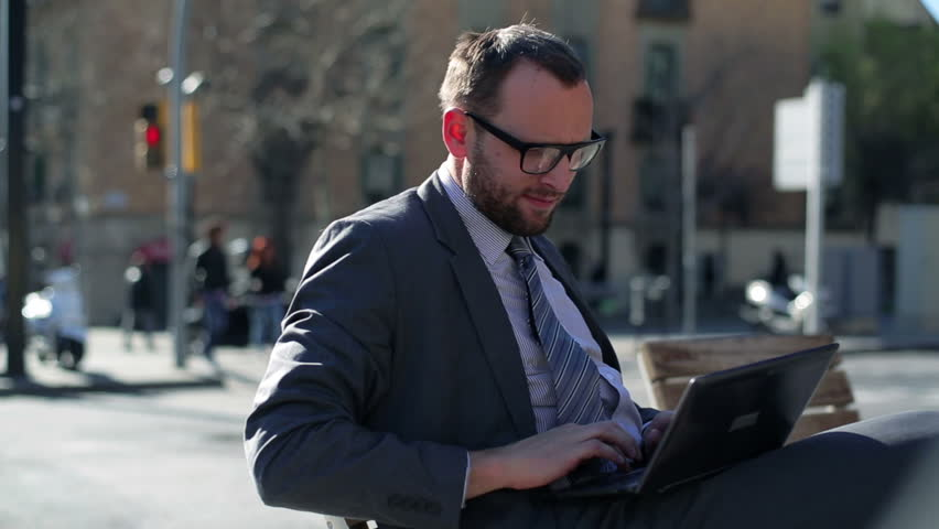 Businessman working on laptop and sitting on street bench, steadycam shot.    Shutterstock HD Video #6081452
