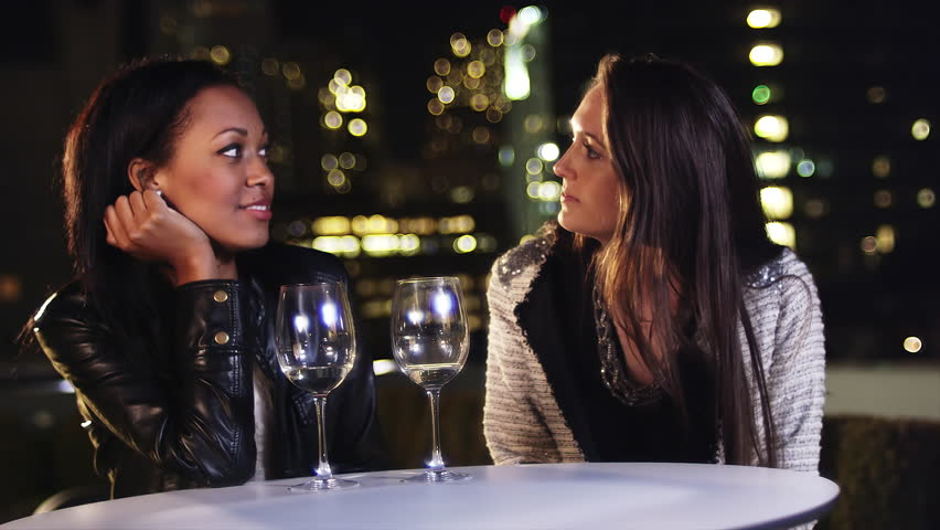 Two girlfriends sit at a table with wine glasses on a rooftop at night | Shutterstock HD Video #6081845