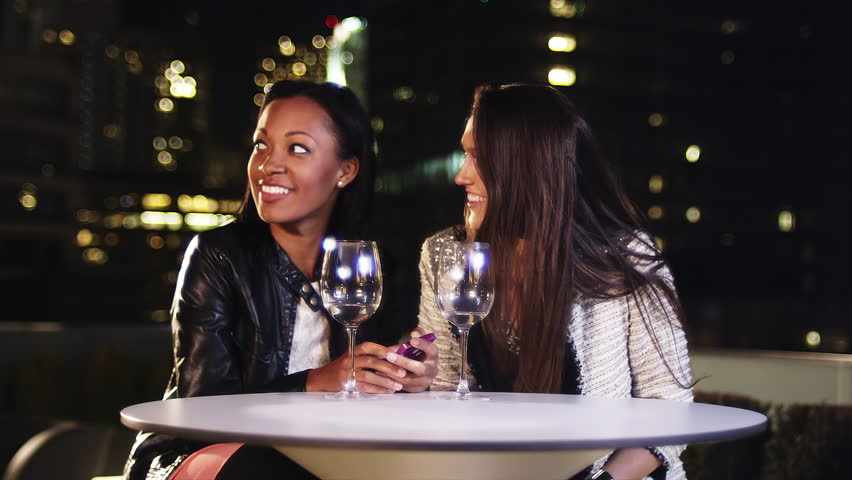 Two girlfriends sit at a table with wine glasses on a rooftop at night, when two men approach them and sit down #6096419