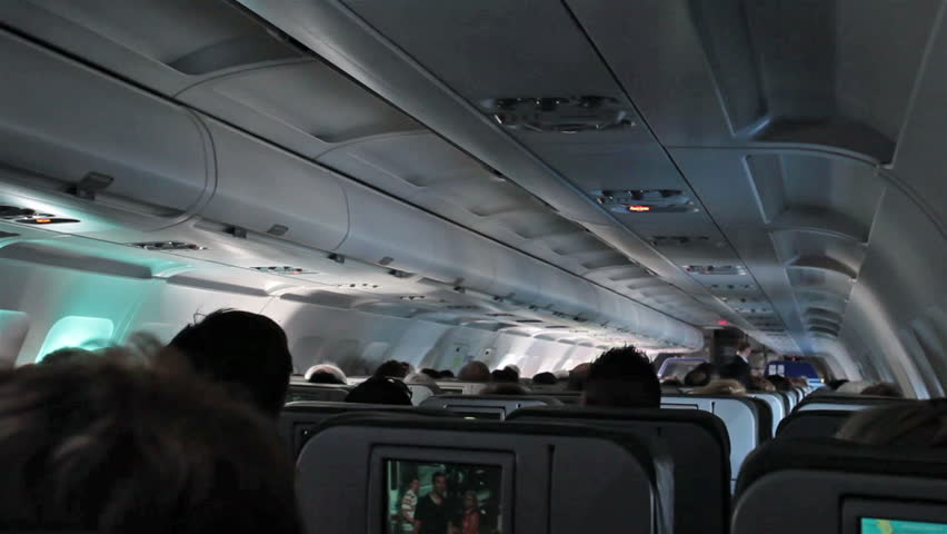 ORLANDO, FLORIDA - JAN 2014: International flight crowded passenger compartment. Turbulence as passengers are bounced around flight cabin. Commercial airline over landscape, ocean, and terrain. | Shutterstock HD Video #6128177